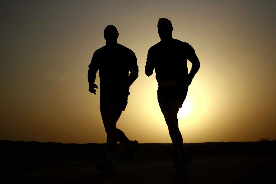 Silhouette of two men running